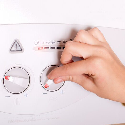 Woman turning water heater temperature on gas heater