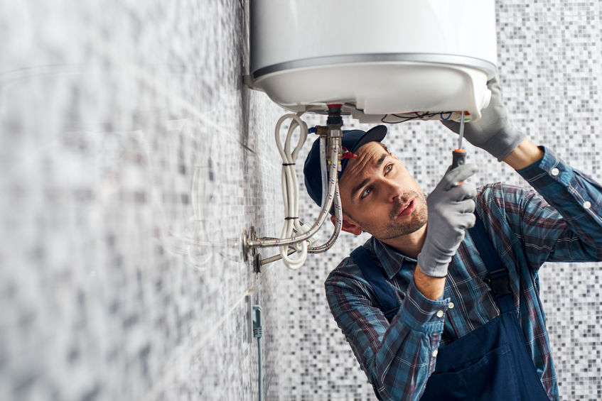 Worker set up electric heating boiler at home.